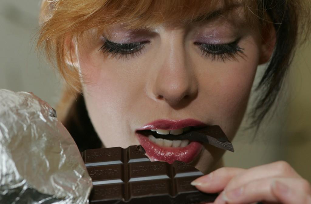 21.03.2006 / junge Frau (model released) beißt in eine dunkle Schokolade &Halle bankverbindung : copyright Steffen Schellhorn Stadtsparkasse Halle / BLZ: 80053762 / Kto: 489317950